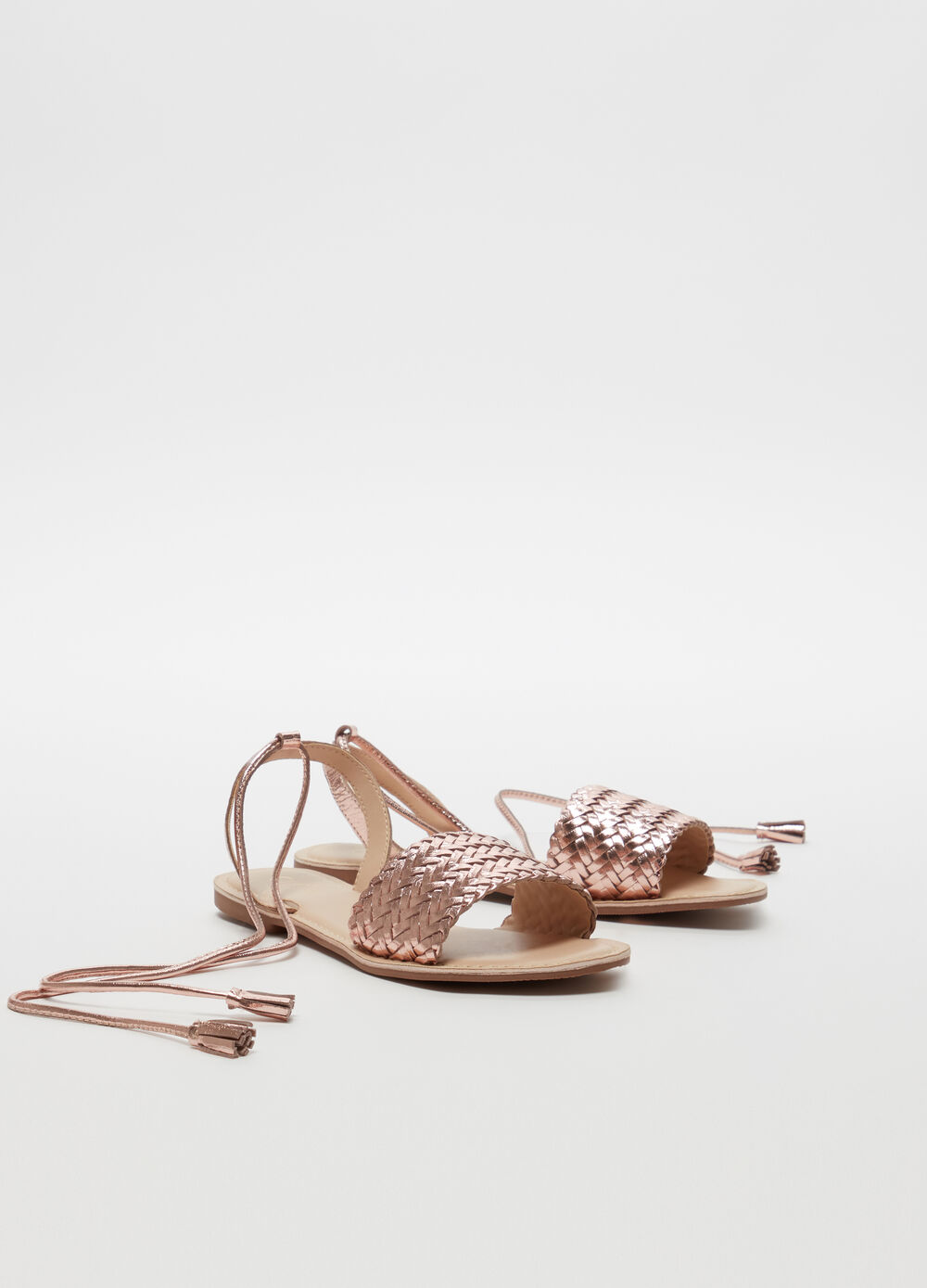 Gold-coloured metallic braided leather thong sandals with laces on the ankles