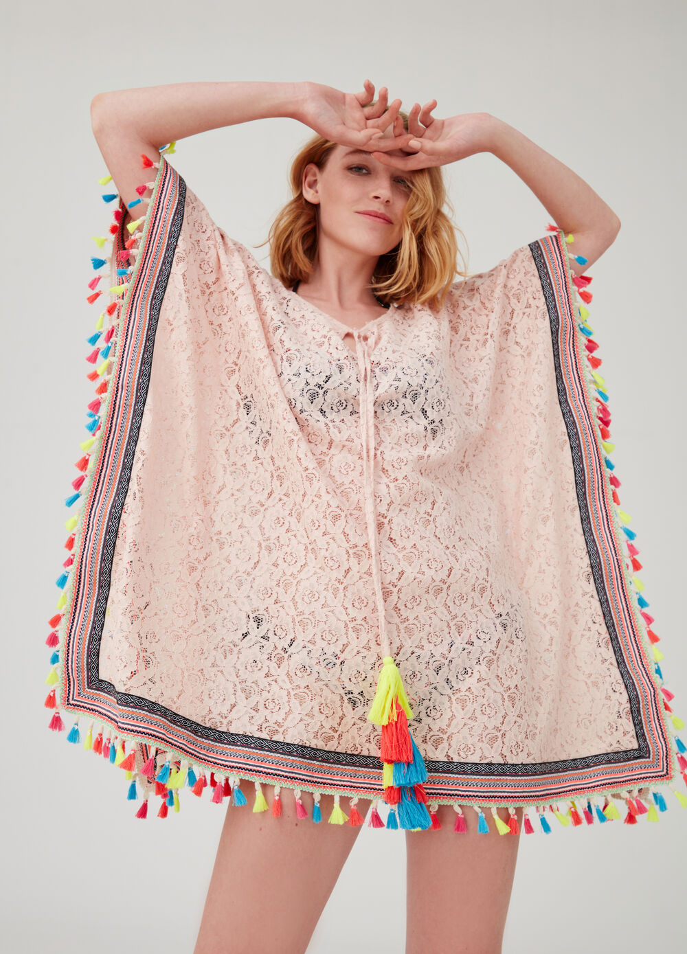 Lace-effect poncho with pattern and tassels